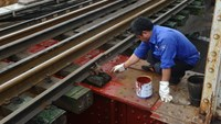 A file photo shows a Vietnamese worker checking a railroad section. Japan has temporarily suspended official development aid to Vietnam over a bribery case involving an urban railway project, officials said June 3. Photo credit: AFP