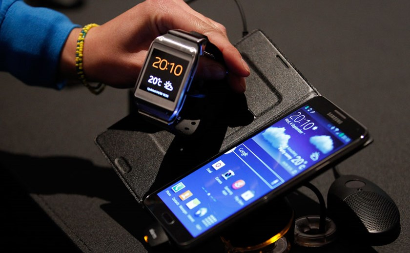 A journalist looks at a Samsung Galaxy Gear smartwatch (L) and Galaxy Note 3 after their launch at the IFA consumer electronics fair in Berlin, September 4, 2013. Photo: Reuters
