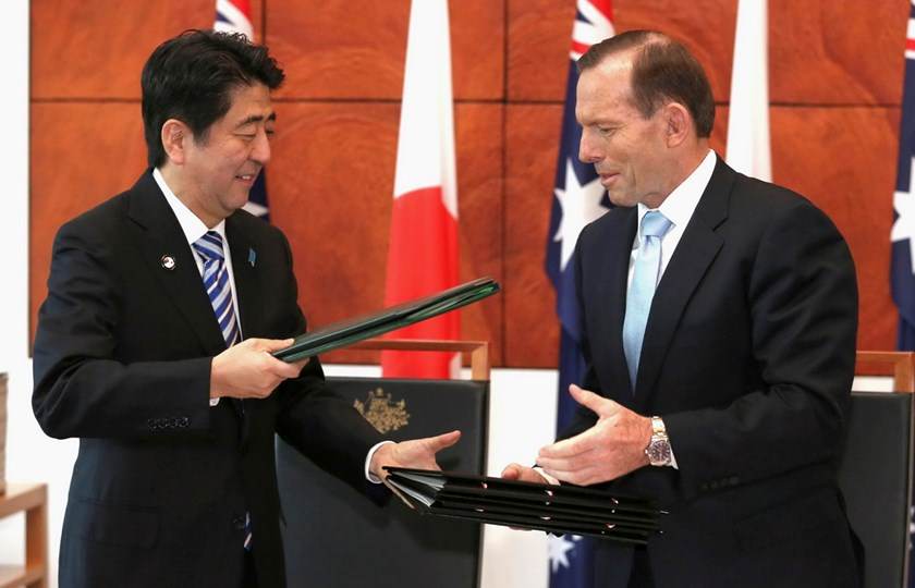 Japanese Prime Minister Shinzo Abe (L) and Australian Prime Minister Tony Abbott exchange documents after signing the Japan-Australia Economic Partnership Agreement and Agreement on the Transfer of Defence Equipment and Technology, in the Mural Hall at Pa