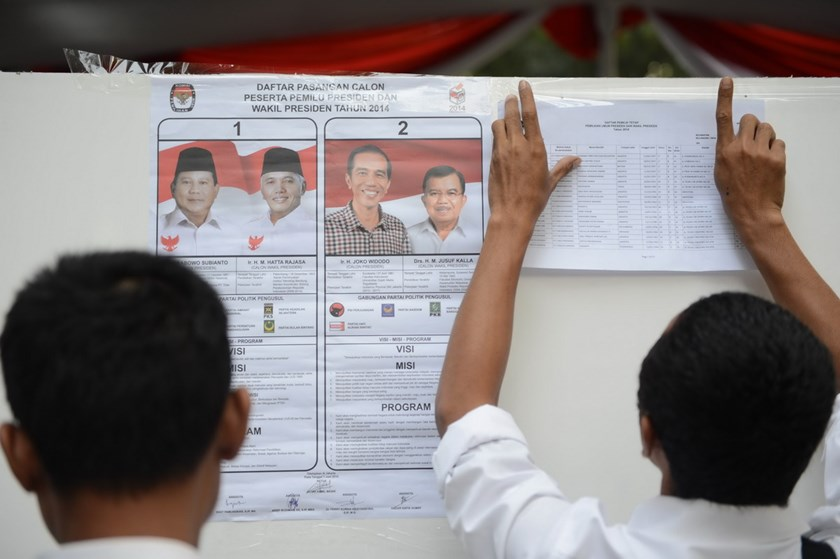 Poll workers post voters list at a polling center in Jakarta next to a poster showing the two presidential candidates Prabowo Subianto (L) with running mate Hatta Rajasa and Joko Widodo with running mate Jusuf Kalla (R) as voting opens in Jakarta on July