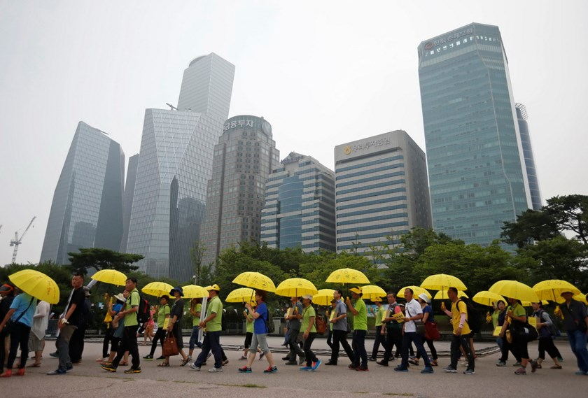 People holding yellow umbrellas in support of victims of the mid-April Sewol ferry disaster, carry boxes containing signatures of South Koreans petitioning for the enactment of a special law after the disaster, as they march towards the National Assembly