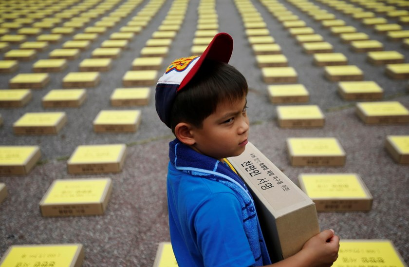 A boy holds a box containing signatures of South Koreans petitioning for the enactment of a special law after the mid-April Sewol ferry disaster, at Yeouido Park in Seoul July 15, 2014. The petition is demanding the government for an impartial investigati