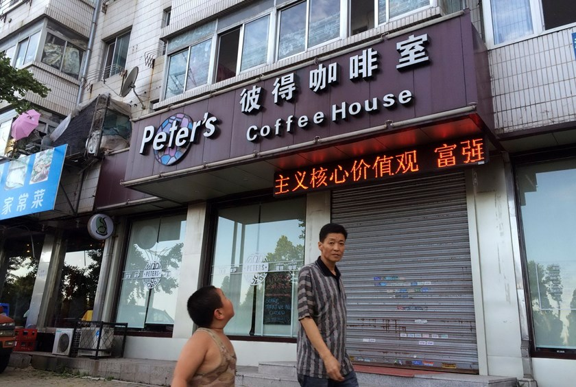 A boy looks up as he walks past the closed coffee shop owned by Canadian couple Kevin Garratt and Julia Dawn Garratt in Dandong, Liaoning province, August 5, 2014. Photo: Reuters