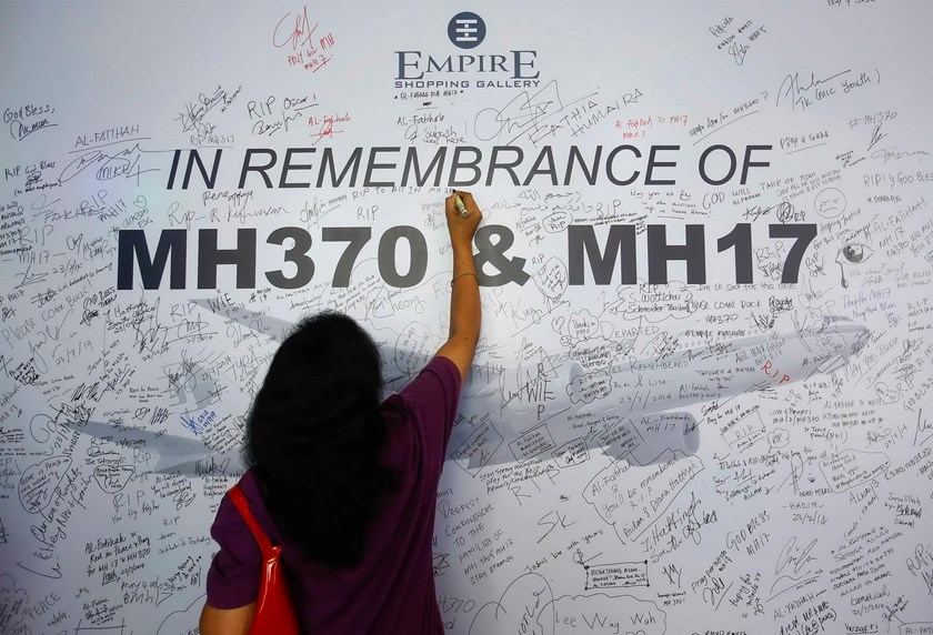 A woman writes a message on a dedication board for the victims of the downed Malaysia Airlines Flight MH17 airliner and the missing Flight MH370, in Subang Jaya outside Kuala Lumpur July 23, 2014. Photo: Reuters