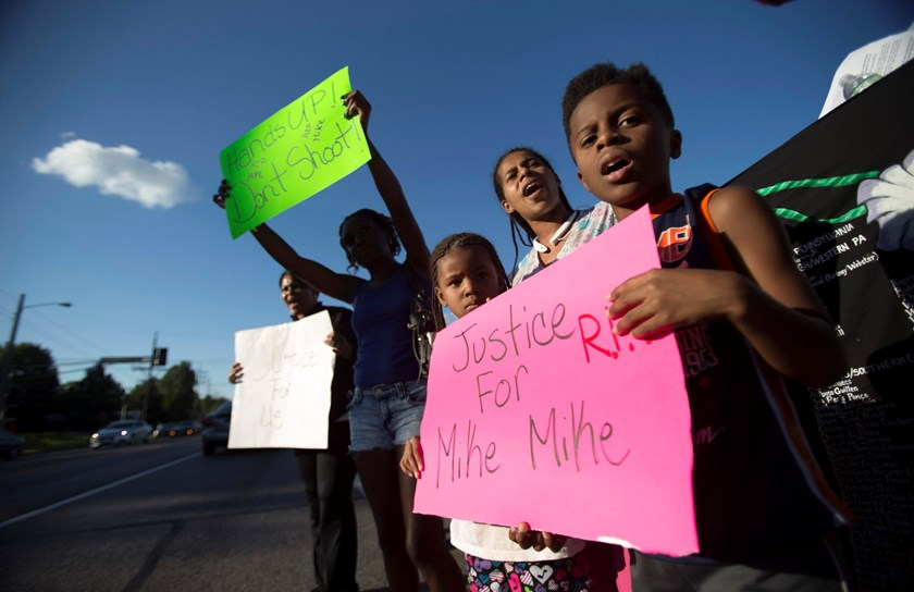 Lisa Kemp chants with children Xavier and Zyniyah while protesting the death of black teenager Michael Brown in Ferguson, Missouri August 12, 2014. Photo: Reuters