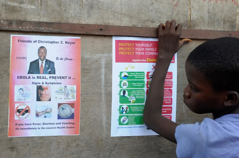A boy stands near posters displaying a government message against Ebola at Duwala market in Monrovia August 17, 2014. To try to control the Ebola epidemic spreading through West Africa, Liberia has quarantined remote villages at the epicentre of the virus