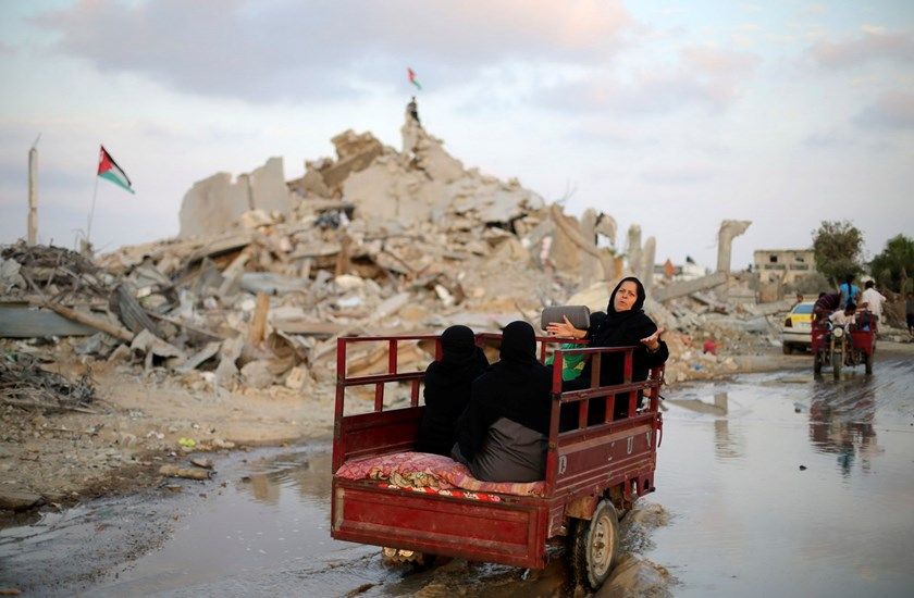 Palestinians ride in a motorbike rickshaw past the ruins of a house, which witnesses said was destroyed during the Israeli offensive, on the fifth day of ceasefire in Khan Younis in the southern Gaza Strip August 18, 2014. Photo: Reuters