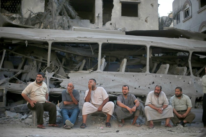 Palestinians sit in front of a bus that witnesses said was destroyed during an Israeli airstrike in Gaza City August 20, 2014. Hamas militants in the Gaza Strip fired rockets at Israel for a second day on Wednesday after fighting resumed with the collapse