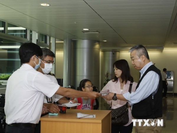 Health workers at the Ho Chi Minh City's Tan Son Nhat Airport check passenger's declarations. Vietnam has introduced mandatory temperature checks at its two major international airports in Hanoi and Ho Chi Minh City to try to prevent passengers bringing t