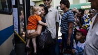 A woman holding her child, gets on a bus with other people at the south station in Donetsk on August 20, 2014. Photo: AFP