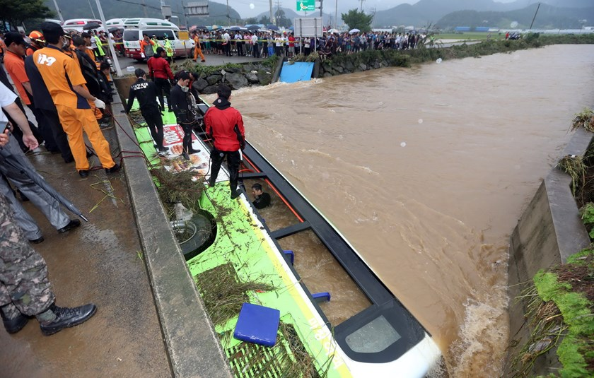 In a photo taken on August 25, 2014, rescue workers attempt to secure a bus submerged by floodwaters in the southeastern town of Changwon. Five people were killed and five others missing as heavy rains pummelled the southern part of South Korea, rescuers