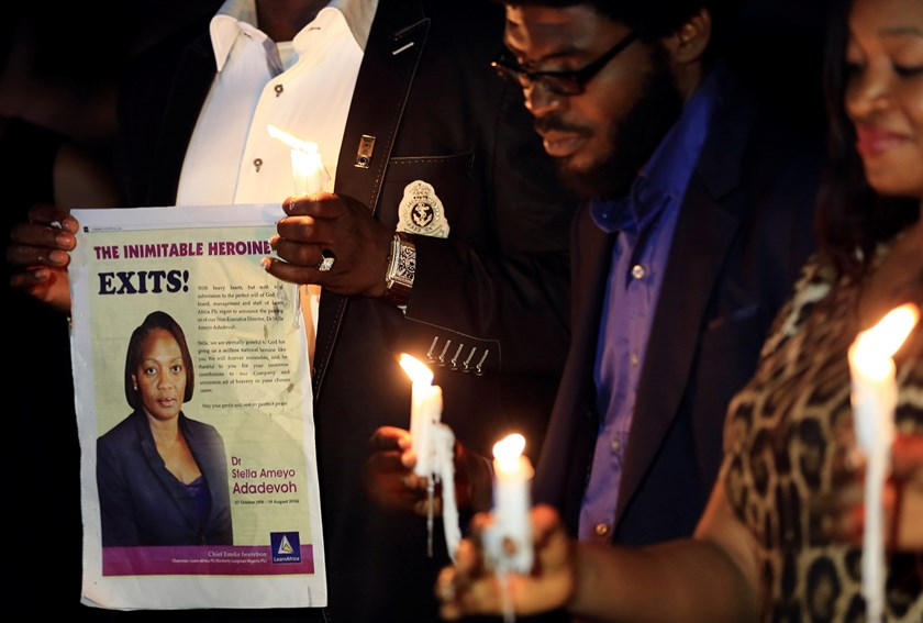 "A campaigner of ""#Bring Back Our Girls"" shows an image of Ameyo Stella Adadevoh during a candlelight vigil for Adadevoh and other Ebola victims in Abuja August 26, 2014. Adadevoh, a consultant physician and endocrinologist, died after contracting the dead"