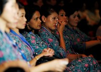 A Malaysia Airlines air stewardess wipes her eyes during a memorial for victims of MH370 and MH17 at Malaysia Airlines headquarters in Kuala Lumpur July 25, 2014. The 19,500 staff of Malaysia Airlines (MAS) face a new ordeal - a quarter of them may lose t