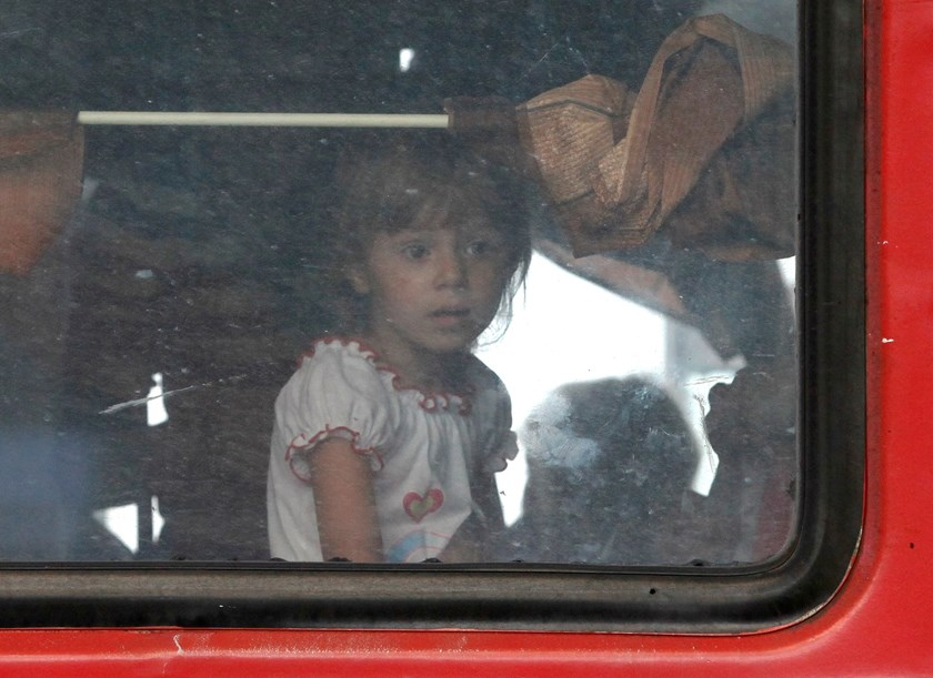 A child looks out of a train window as people who have fled from fighting in eastern regions of Ukraine arrive to a railway station on their way to a temporary accommodation in the local cities and settlements of Siberia, in Krasnoyarsk, September 1, 2014