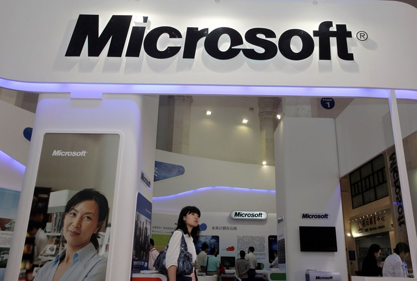 A file photo shows a visitor walking past a Microsoft booth at a computer software expo in Beijing. Photo: Reuters
