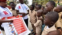 Volunteers wearing t-shirts of the United Nations Development Program (UNDP) show a placard to raise awareness on the symptoms of the Ebola virus to students of the Sainte Therese school, in the Koumassi district, in Abidjan, on September 15, 2014, on the
