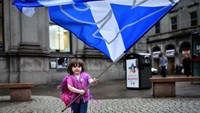 A child plays with a pro-independence 'Yes' flag on the streets of Aberdeen in Scotland, on September 15, 2014, ahead of the referendum on Scotland's independence. Photo: AFP