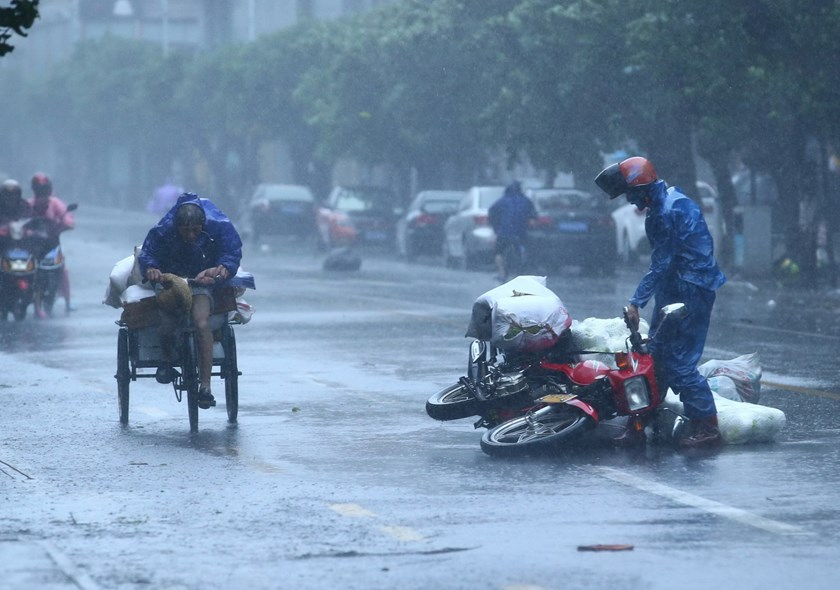 A man picks up his motorcycle amid heavy rainfall and strong winds as typhoon Kalmaegi makes landfall in Haikou, south China's Hainan province. Photo: AFP