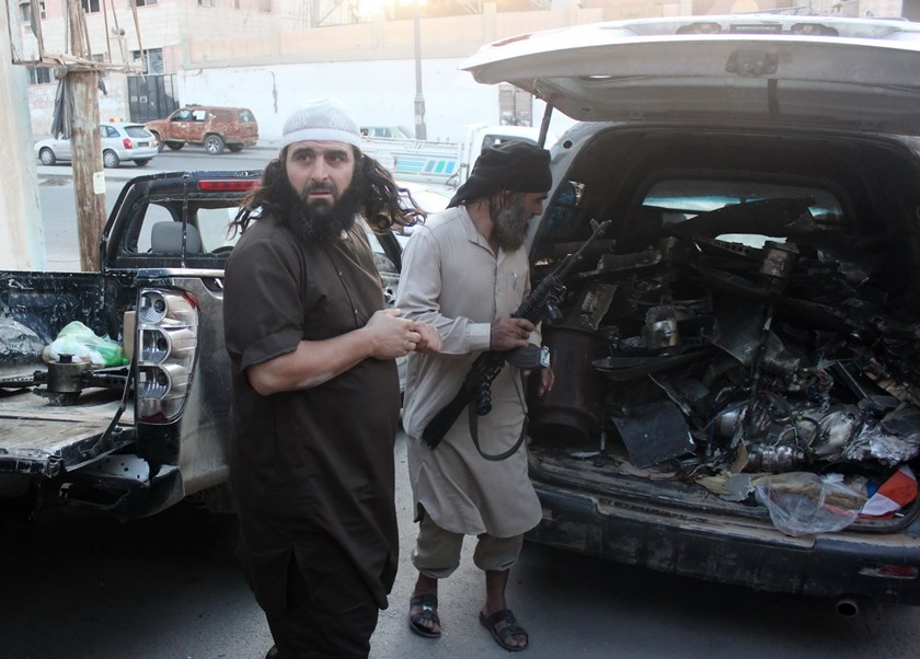 Fighters from the Islamic State group load a van with parts that they said was a US drone that crashed into a communications tower in Raqqa early on September 23, 2014. Photo: AFP