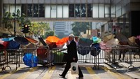 A man walks by a barricade of metal fence and umbrellas on a street at the central financial district, near the government headquarters in Hong Kong September 30, 2014. As tensions subsided, weary protesters dozed or sheltered from the sun beneath umbrell