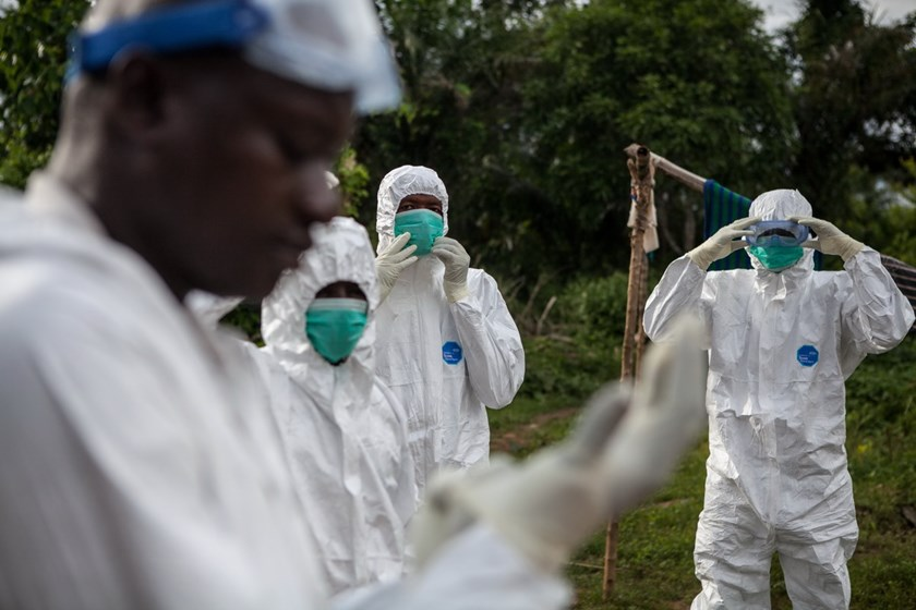A specialized Ebola inhumation team wear protective suits, on October 6, 2014 in Mananeh. Ebola may only be present in a few African nations, but fears over the crippling outbreak are infecting economies across the continent and may put its envy-inducing