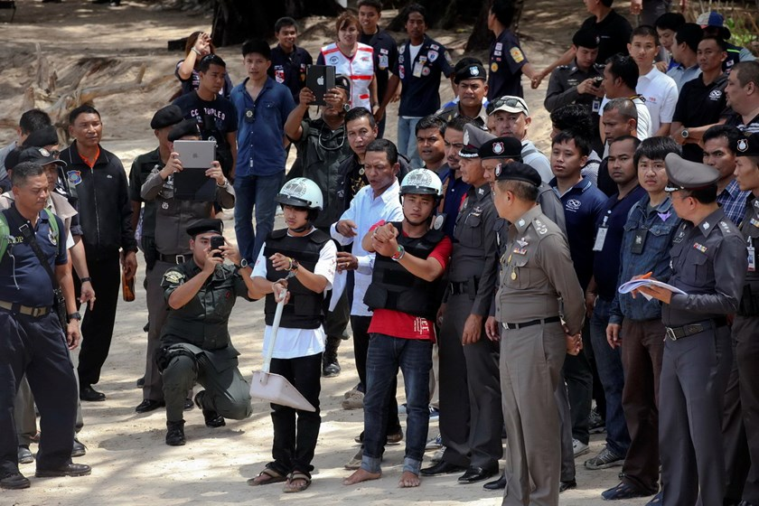 Two workers from Myanmar (wearing helmets and handcuffs), suspected of killing two British tourists on the island of Koh Tao last month, stand near Thai police officers during a re-enactment of the alleged crime, where the bodies of the tourists were foun