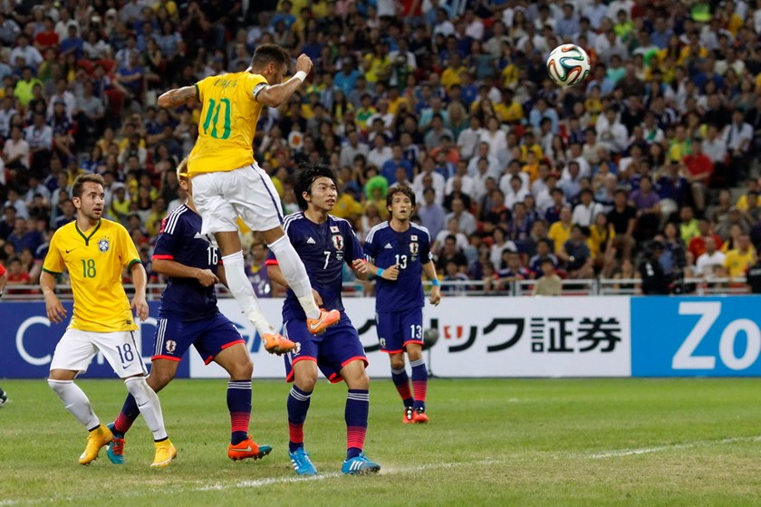 Brazil's Neymar (10) heads the ball to score his fourth goal against Japan during their friendly soccer match at the national stadium in Singapore October 14, 2014. Photo: Reuters