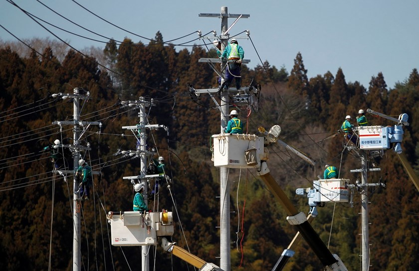 Workers climb poles to fix power lines in Minamisanriku, Miyagi prefecture, after the area was devastated by the March 11 magnitude 9.0 earthquake and tsunami, in this April 6, 2011 file photo. Photo: Reuters