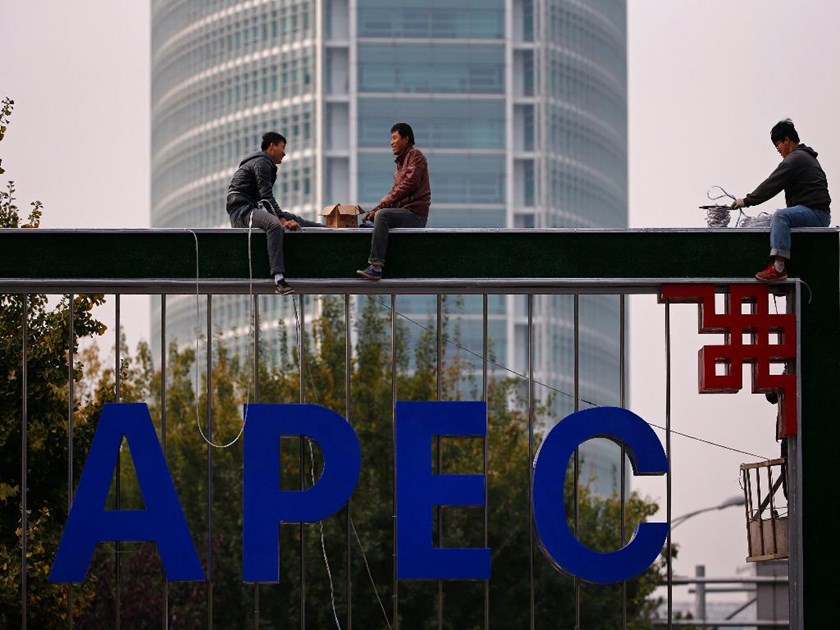 "Workers install lighting on an APEC sign post at the financial district in Beijing, October 28, 2014. Countries at an Asia-Pacific summit in Beijing pledged to pursue ""flexible"" fiscal policies to support the world economy and job creation, their finance"