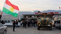 A man waves a Kurdistan flag as a Turkish military truck escorts a convoy of peshmerga vehicles at Habur border gate, which separates Turkey from Iraq, near the town of Silopi in southeastern Turkey, October 29, 2014. Photo: Reuters