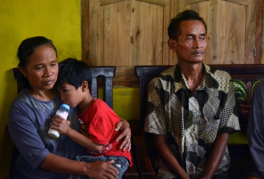 Indonesian parents of Sumarti Ningsih, the Indonesian woman was murdered in Hong Kong, mother Suratmi, (L) carrying Muhammad Hafidz Arnovan, five year old son of Sumarti and father Ahmad Kaliman (R) look on in their family residence in Cilacap, in a port