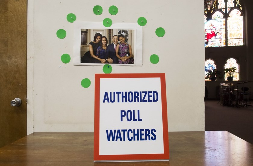 "A photograph of US President Barack Obama, First Lady Michelle Obama and their daughters appears inside a polling place alongside the ""Authorized Poll Watchers"" designated area as voters cast their ballots for the midterm elections in Washington, DC, Nove"