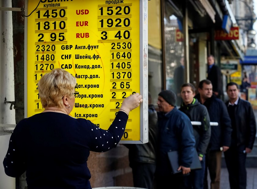 An exchange office worker changes numbers indicating the conversion rates outside a currency exchange office in central Kiev November 10, 2014. Photo: Reuters