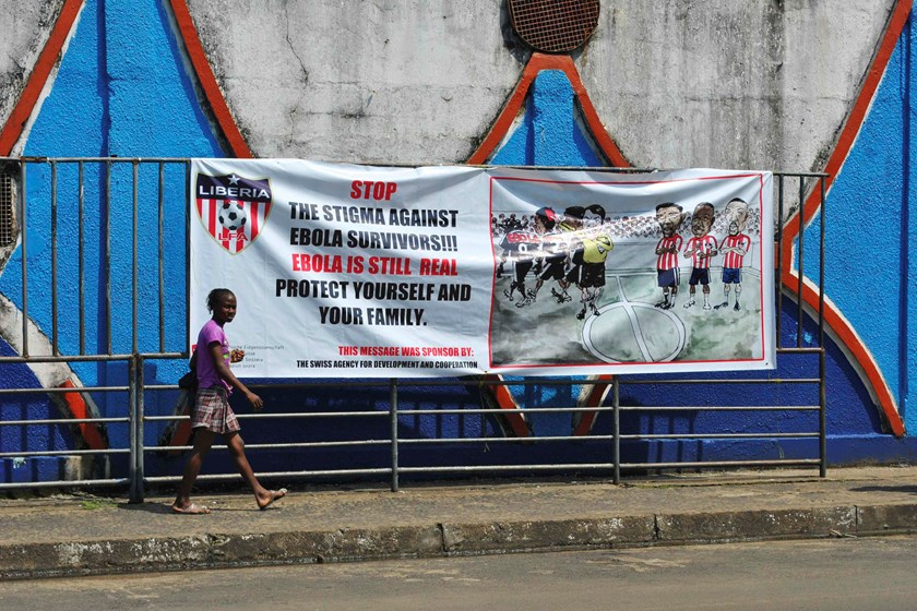 A woman walks pass an Ebola virus awareness campaign poster in Monrovia, December 8, 2014. Liberia is the country hardest hit by the epidemic and has recorded more than 3,000 deaths out of a total from Liberia, Sierra Leone and Guinea of 6,055 victims, ac
