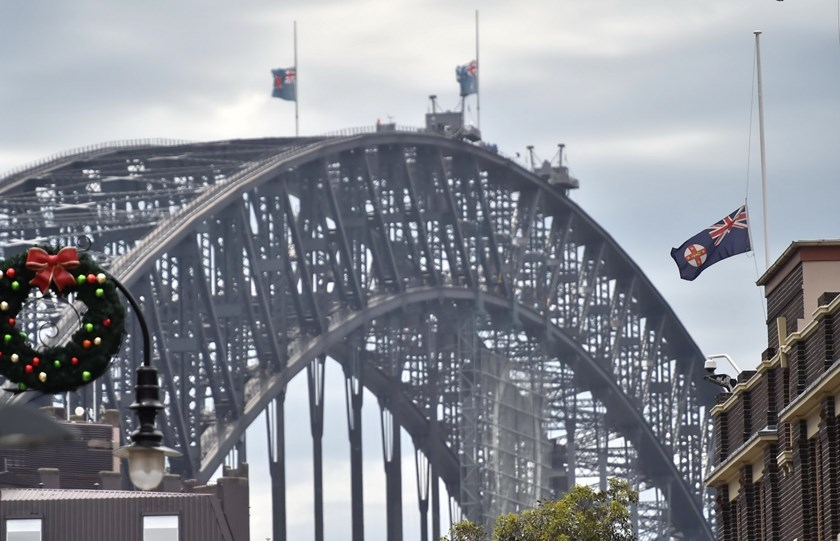 Australian flags fly at half mast on Sydney Harbour bridge following the fatal siege in the heart of Sydney's financial district on December 16, 2014. Photo: AFP