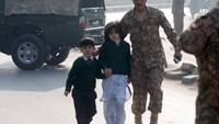A soldier escorts schoolchildren from the Army Public School that is under attack by Taliban gunmen in Peshawar, December 16, 2014. Photo: Reuters