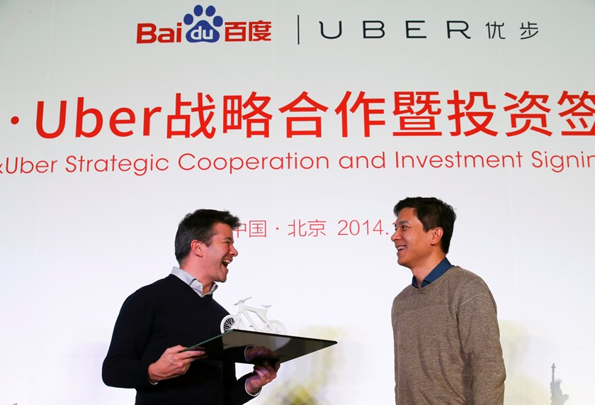 Uber CEO Travis Kalanick (L) smiles after receiving a gift from Baidu Inc. Chairman and CEO Robin Li after signing their documents during the Baidu and Uber strategic cooperation and investment signing ceremony at Baidu's headquarters in Beijing December