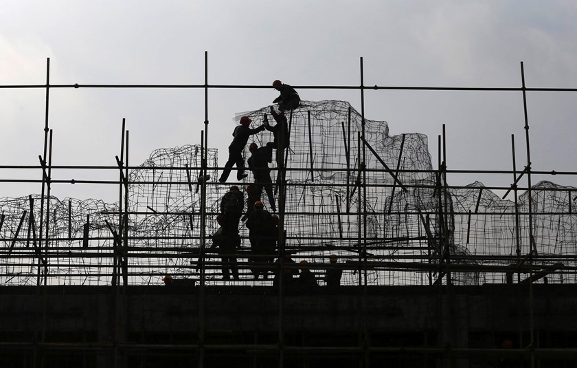 Laborers work on the scaffoldings at a construction site in Kunming, Yunnan province, December 22, 2014. Photo: Reuters
