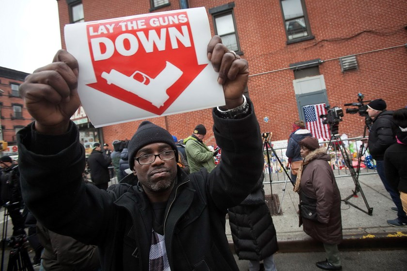 A protester hold up a sign at a makeshift memorial at the site where two police officers were shot in the head in the Brooklyn borough of New York, December 22, 2014. Photo: Reuters