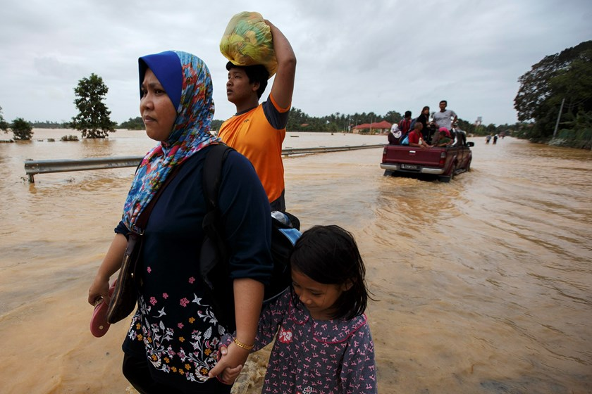People carry their belongings as they evacuate through a flooded street, on the outskirts of Kota Bharu in Kelantan December 29, 2014. Photo: Reuters
