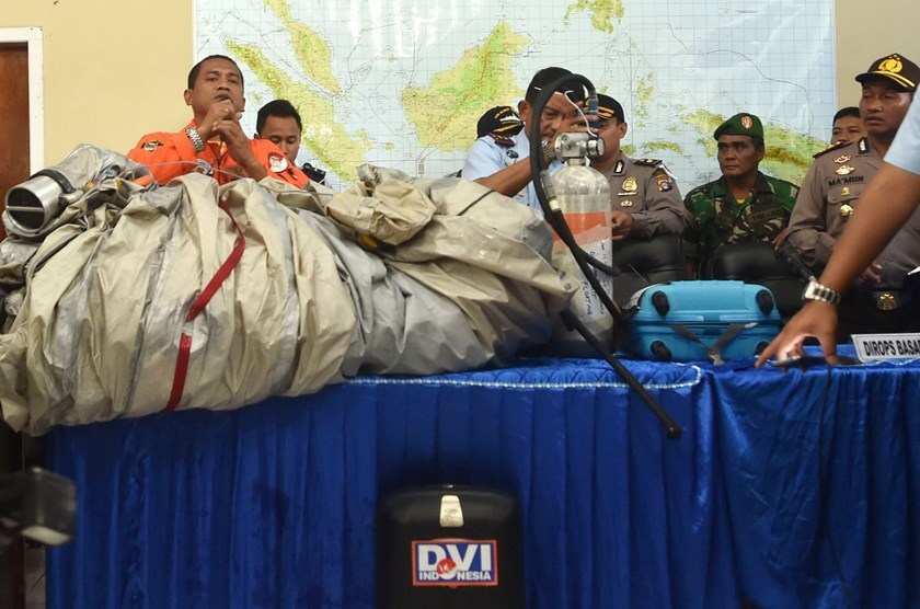 Members of the Indonesian air force show items retrieved from the Java sea during search and rescue operations for the missing AirAsia flight QZ8501, in Pangkalan Bun, Central Kalimantan on December 30, 2014. Photo: AFP