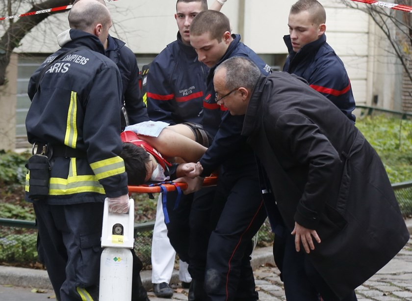 Firefighters carry a victim on a stretcher at the scene after a shooting at the Paris offices of Charlie Hebdo, a satirical newspaper, January 7, 2015. Photo: Reuters