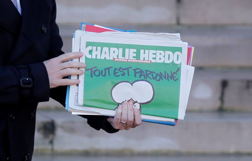 "French Prime Minister Manuel Valls holds a copy of Charlie Hebdo with the title ""Tout est pardonne"" (""All is forgiven"") as he leaves the weekly cabinet meeting at the Elysee Palace in Paris January 14, 2015. Photo: AFP"