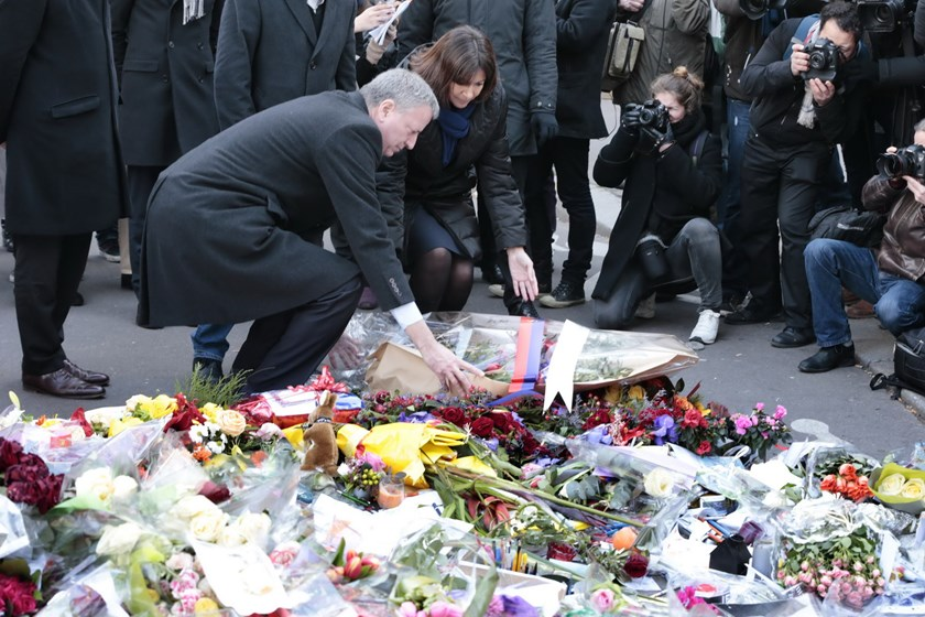 Mayor of New York Bill de Blasio and Mayor of Paris Anne Hidalgo place flowers near the offices of French satirical weekly Charlie Hebdo in Paris on January 20, 2015, to pay tribute to the twelve people killed when gunmen armed with Kalashnikovs and a roc