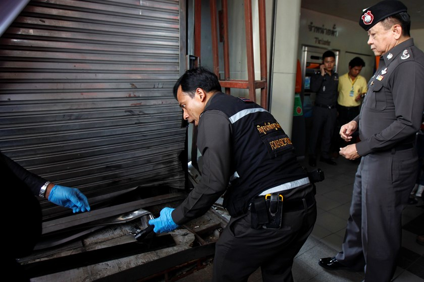 Police forensic experts work at the site of a blast on an elevated walkway linking the overhead rail line to the mall in central Bangkok February 2, 2015. Photo: Reuters