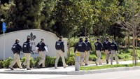 "Federal agents walk past the Carlyle Apartments, the location of a suspected ""baby tourism operation, in Irvine California March 3, 2015. Photo: Reuters"