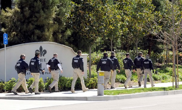 """Federal agents walk past the Carlyle Apartments, the location of a suspected """"baby tourism operation, in Irvine California March 3, 2015. Photo: Reuters"""