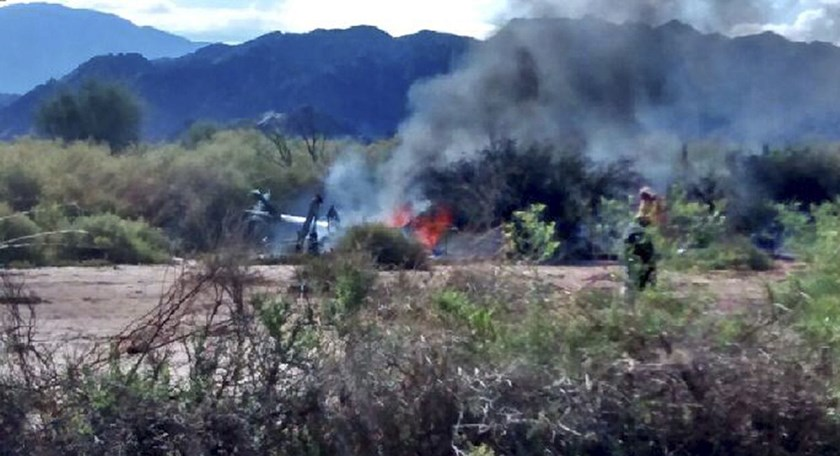 A picture released by NA showing the wreckage of a helicopter burning in flames after colliding mid-air with another chopper near Villa Castelli, in the Argentine province of La Rioja, on March 9, 2015. All ten people aboard the helicopters died, includin
