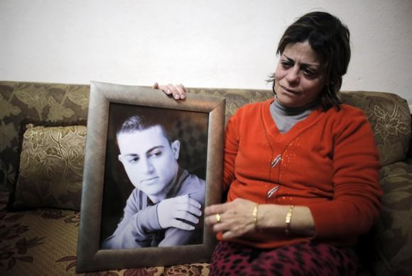 The mother of Muhammad Musallam, an Israeli Arab held by Islamic State in Syria as an alleged spy, weeps as she holds his photograph in her East Jerusalem home February 12, 2015. Photo: Reuters
