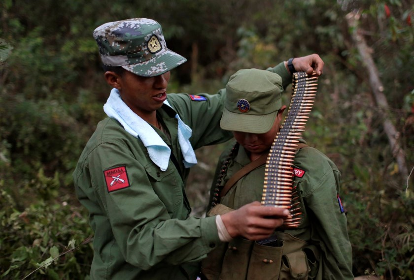 A rebel soldier of Myanmar National Democratic Alliance Army (MNDAA) places a machine gun bullet belt around the neck of another soldier at a military base in Kokang region, March 10, 2015. Photo: Reuters